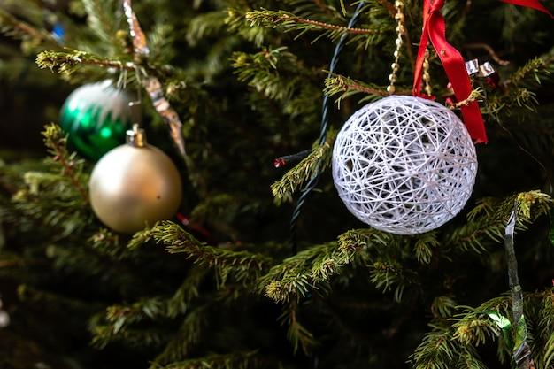 さまざまなカラフルなクリスマスの飾りがスプルースの枝にぶら下がっていました。