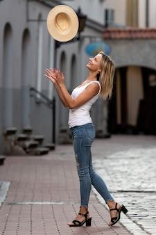 古い町の通りの真ん中に長いブロンドの髪、白いブラウス、ブルージーンズと明るい帽子の美しい女性