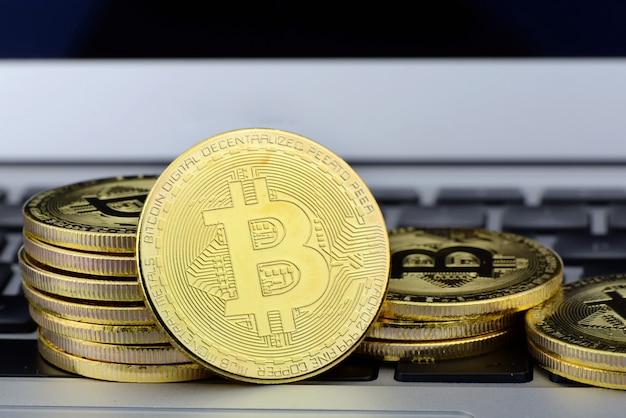 ノートパソコンのキーボード上のビットコインコインのスタック