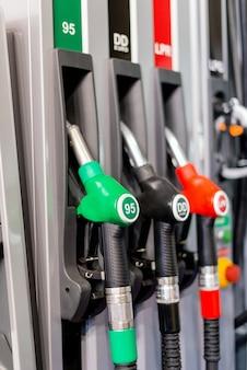 カラフルなガソリンポンプ充填ノズル、昼間のサービスのガソリンスタンド。