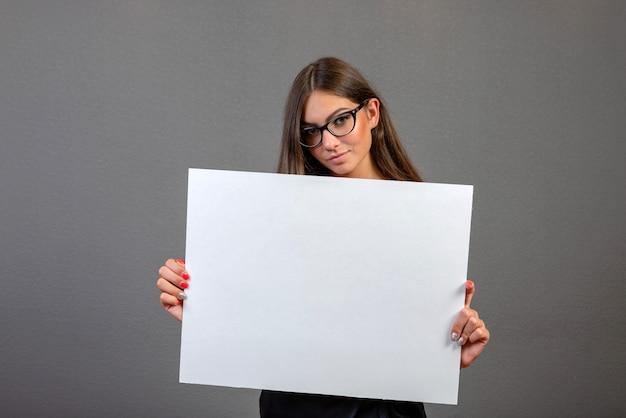 灰色の背景に分離されたブランクの看板を保持している美しい女性