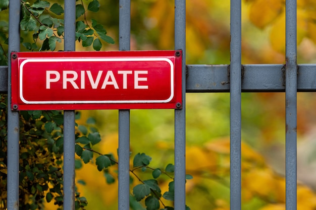 Красный металлический знак с частной надписью на декоративном металлическом заборе