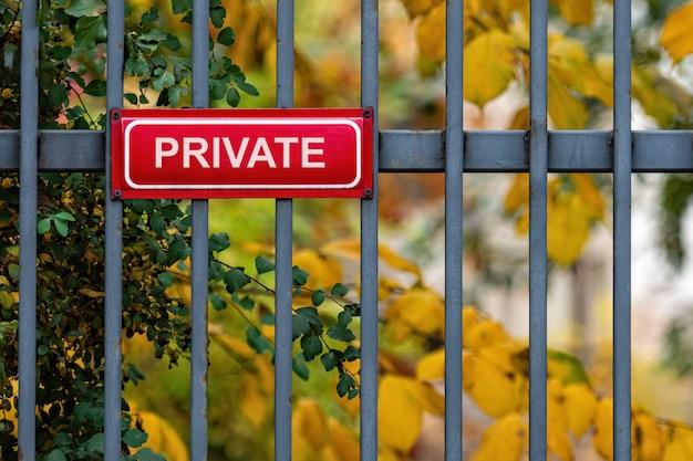 Красный металлический знак с надписью - частный на декоративном металлическом заборе, расфокусированные осенние деревья в фоновом режиме