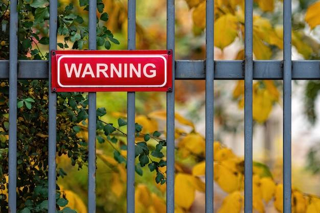 Красный металлический знак с надписью предупреждение на декоративном металлическом заборе