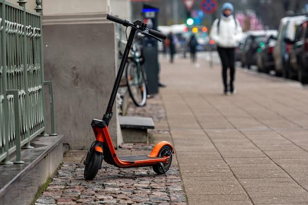 Электрический скутер на стоянке на тротуаре в риге, латвия