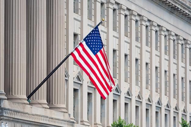 歴史的な建物の正面にアメリカの国旗