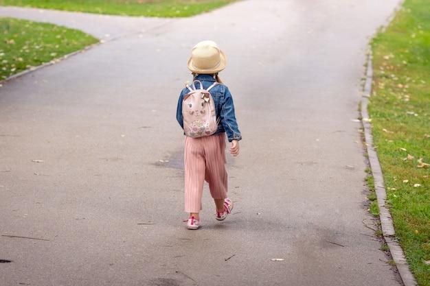 Маленькая девочка с рюкзаком идет по тротуару.