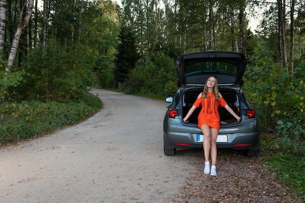 車のブーツの端に座って、道路の脇に笑顔の若い女性