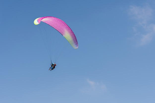 澄んだ青い空を背景に山々の上のスイスアルプスのパラグライダー