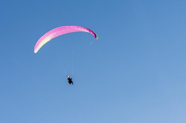 Параглайдинг в швейцарских альпах над горами против ясного голубого неба.
