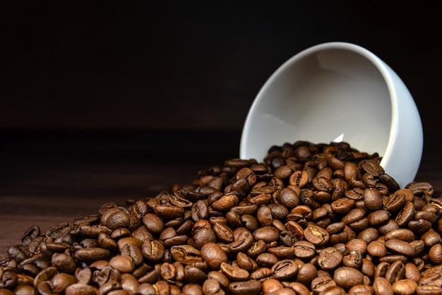 木製のテーブルに白いマグカップから注ぐコーヒー豆