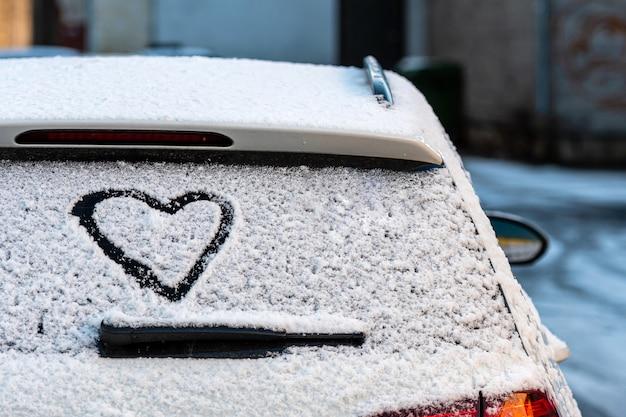 雪に覆われた車のリアウィンドウにハート形