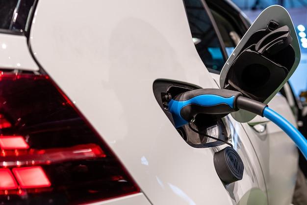 電気自動車充電用の電源。電気自動車の充電ステーション。充電中の電気自動車に差し込まれている電源のクローズアップ。