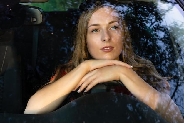 長い髪の若い美しい女性が車のホイールに座って、フロントガラスのまぶしさを夢見て見ていました。