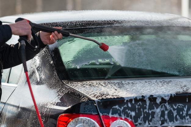 セルフサービスのタッチ洗浄のない車。水と泡で洗う。
