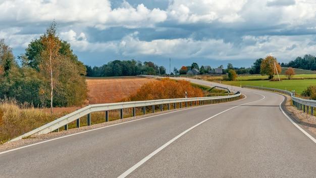 Осенний пейзаж с асфальтированной дороги и леса.