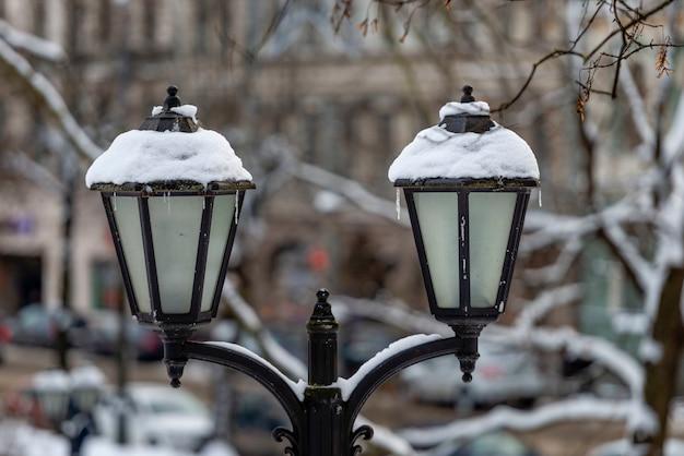 都市公園への雪に覆われた古代のランタン