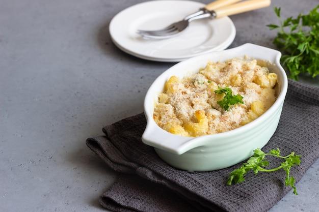 グラタン皿のベシャメルソースのグリーンピースと魚のパスタキャセロール