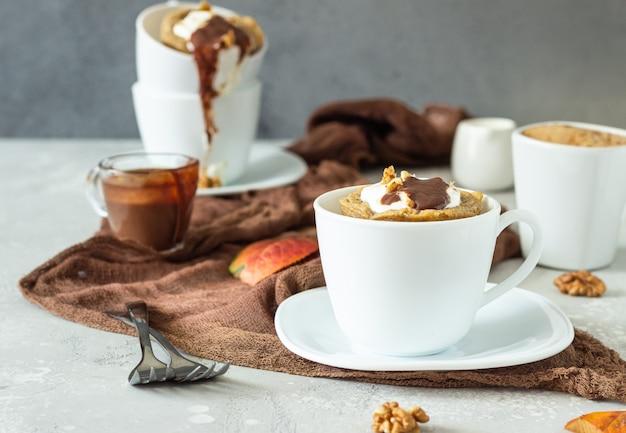 ホイップクリーム、キャラメルソース、クルミの白いセラミックマグカップとニンジンまたはカボチャのマグカップカップケーキ。
