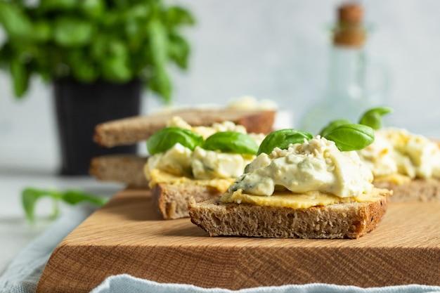 サンドイッチを作るためのバジルと新鮮な食材と卵サラダ、アボカド、フムスのサンドイッチ。