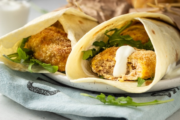 トルティーヤはチキンまたは七面鳥のカツレツ、ルッコラ、サワークリームソースで包みます。
