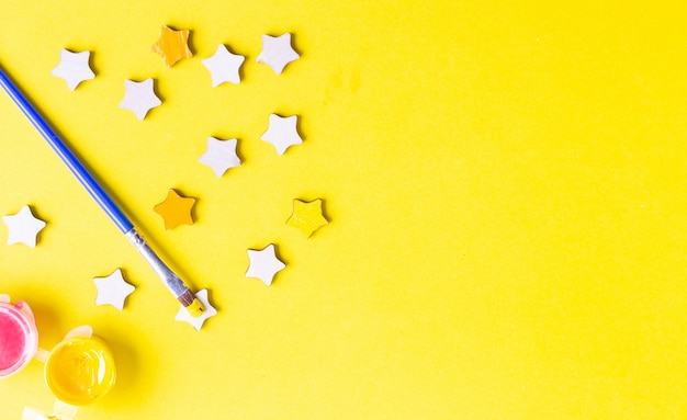 黄色の背景に水彩絵の具、絵筆、星形の構成。