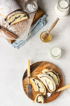 木の板にケシの実のロールまたはシュトルーデルに粉砂糖を振りかけました。