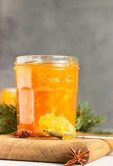 冬のスパイスとモミの枝が付いているガラス瓶にオレンジジャム。
