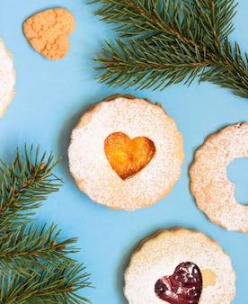 リンツァーのクリスマスまたは新年のクッキーは、青い紙の背景にジャムでいっぱい。
