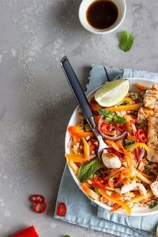 Чаша будды с жареной курицей и морковью, перцем, луком, рисом и зеленью