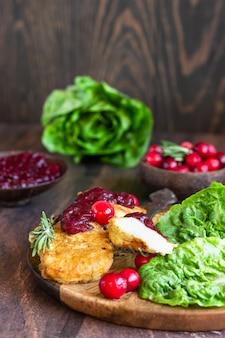 クランベリーソースとグリーンサラダを添えたウィーン風チキンシュニッツェル