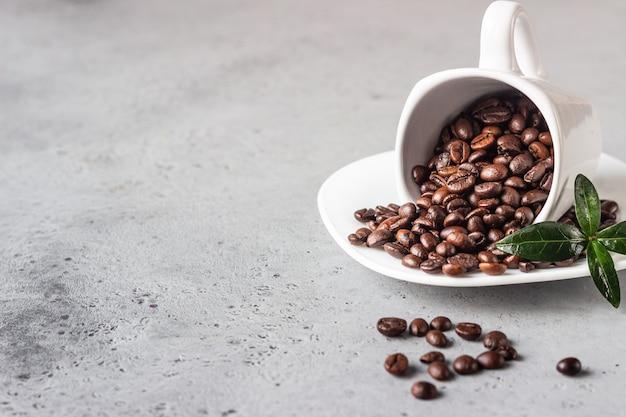 灰色の石の背景にロースト豆とコーヒーカップテキストのコピースペース