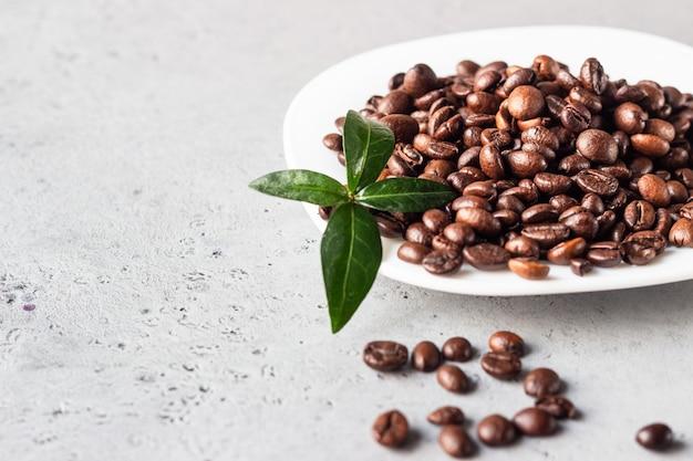 灰色の石の背景にロースト豆と白いコーヒープレートテキストのコピースペース