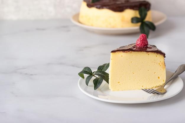 セラミックプレートにチョコレート艶出しで飾られた日本綿のスフレチーズケーキ
