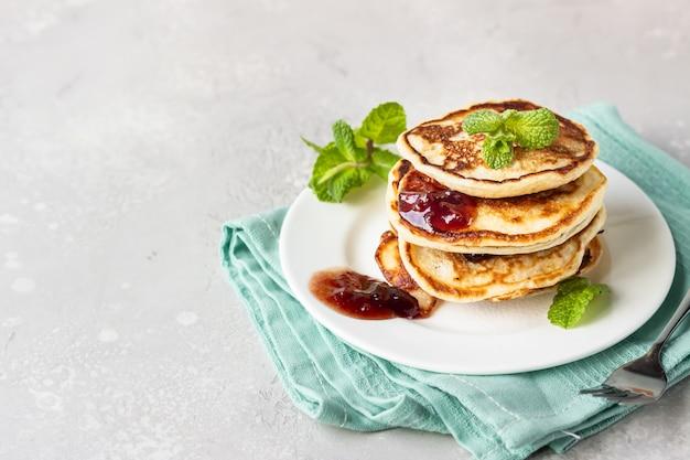 赤いベリージャムとミントのパンケーキ、明るい灰色の石背景アメリカ料理。朝ごはん。