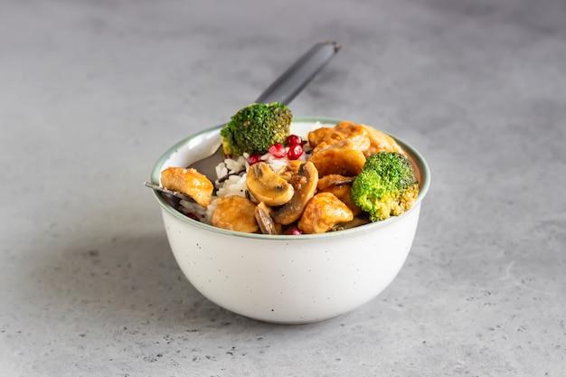 ザクロの種子で飾られたご飯、マッシュルーム、ブロッコリーのカレーチキン