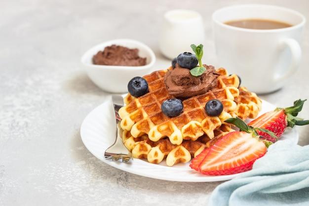 ベルギーワッフル、チョコレートソース、ベリー、ミントのプレート。朝食または昼食。
