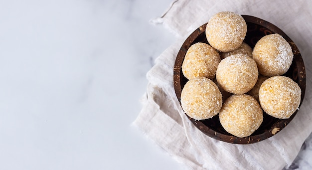 ひよこ豆、ピーナッツバター、木製のボウルにココナッツと健康的なベジタリアンボール