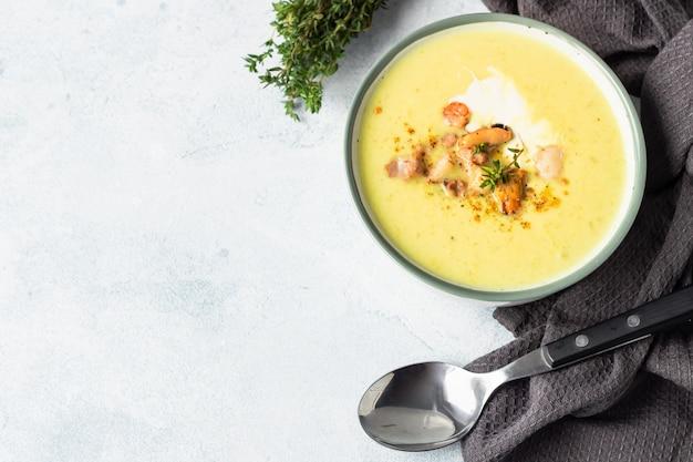 サワークリーム、タイム、コショウを添えたシーフードと濃厚なミルキーチャウダースープ