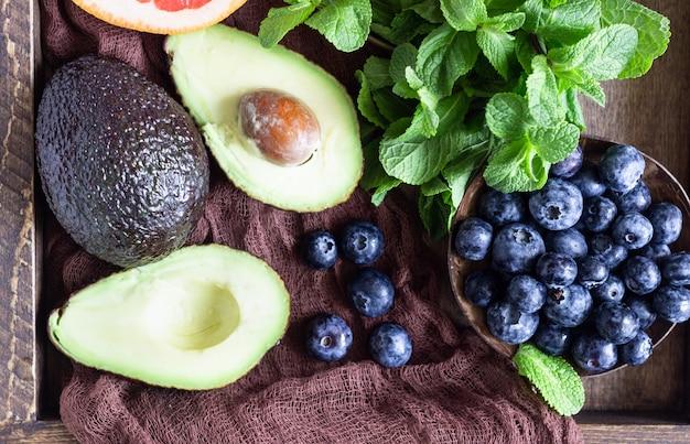 木製トレイに新鮮なブルーベリー、ミント、アボカド、グレープフルーツ。健康食品。食事の選択をクリアします。夏の朝食または昼食。