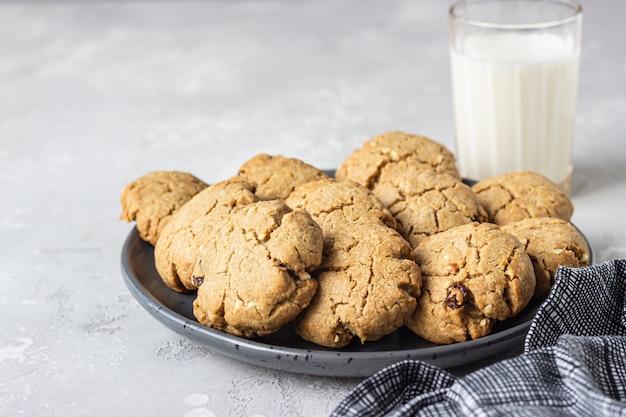 Здоровое веганское печенье с орехами и изюмом на керамической тарелке с молоком
