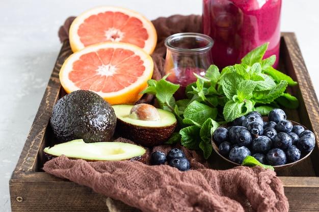 木製トレイにブルーベリー、ミント、アボカド、グレープフルーツと紫のスムージー。健康食品。夏の朝食または昼食。