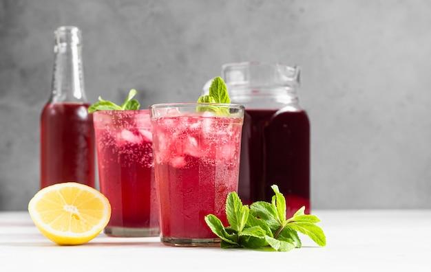 レモンとミントのきらめくピンクのレモネード。夏の飲み物。