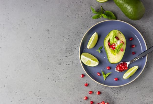 Авокадо с зернами граната, сыром рикотта или сливочным сыром, листьями салата и мятой