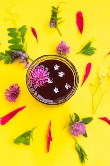Стакан с чаем гибискуса с разными полевыми цветами
