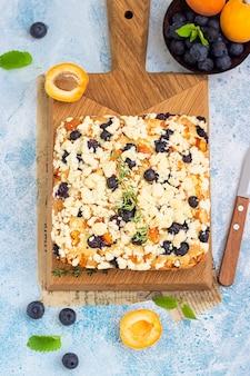 Вид сверху домашнего пирога из черники и абрикоса