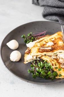 キノコ、モッツァレラチーズ、マイクログリーンを添えたクラシックなオムレツ。朝ごはん。