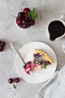 Запеканка из творога с черной вишней, украшенная шоколадом, кокосовой стружкой и мятой