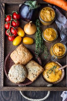 Овощная икра в банках, свежие помидоры, лук, морковь, баклажаны и тимьян подаются с хлебом в деревянном подносе. домашние консервы. веганская кухня. осенний урожай.