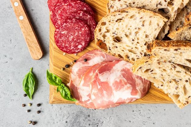木製のまな板で提供される種と豚肉ソーセージとサラミの伝統的な職人パン。ポークソーセージのオープンサンドイッチ。